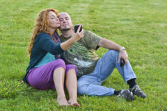 Happy adult married couple sitting on grass with mobile phone Stock Image
