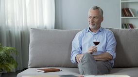 Happy adult person sitting on sofa, drinking red wine and thinking about life. Stock footage Stock Photos