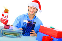 Happy Adult Wearing Santa Hat With So Many Gift. Happy young adult wearing christmas santa hat with many gifts royalty free stock photo
