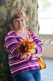 Happy adult woman with a bouquet of colorful autumn leaves Royalty Free Stock Photo