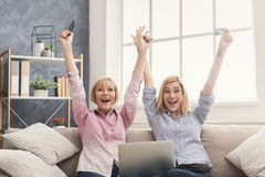 Happy adult woman and daughter using laptop at home. Happy adult women and daughter with raised arms, shopping online with credit card and laptop, copy space Royalty Free Stock Photography