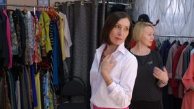 Happy Adult Woman Fitting Blouse Skirt at Store. Beautiful Middle Age Lady Posing in Dressing Room. Caucasian Model in Massive Necklace Smiling to Fashion stock video footage