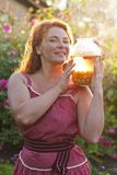 Happy adult woman holding jar with compote of cherries Royalty Free Stock Images