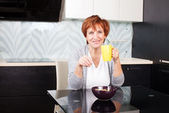 Happy adult woman on kitchen Stock Photography