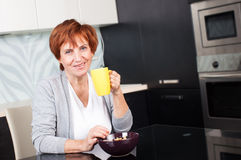 Happy adult woman on kitchen Royalty Free Stock Photos
