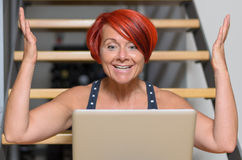 Happy Adult Woman with Laptop Raising her Arms Stock Photo