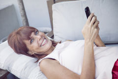 Happy adult woman with mobile phone. Happy adult woman smiling with mobile phone Royalty Free Stock Photography