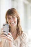 Happy adult woman with mobile phone. Happy adult woman smiling with mobile phone Stock Images
