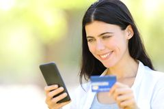 Happy adult woman paying with credit card and phone. Happy adult woman paying on line with credit card and smart phone in a park stock photos