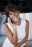 Happy adult woman on the phone. Happy adult woman smiling on the phone Royalty Free Stock Photography