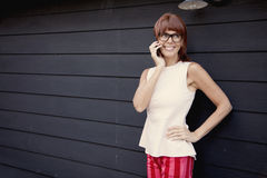 Happy adult woman on the phone. Wearing glasses and smiling Royalty Free Stock Photo