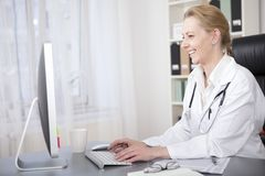 Happy Adult Woman Physician Chatting to Patients Royalty Free Stock Photography
