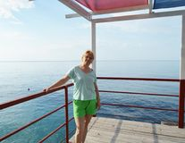 Happy adult woman in shorts posing, smiling against the sea royalty free stock photo