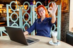 Happy adult woman, sitting in cafe, smiling and showing gesture ok. Indoors in the cafe. royalty free stock images