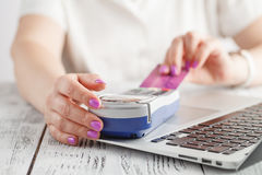 Happy adult woman sitting at home on couch with laptop and credit card. Paying bills and orders. Online shopping and e-commerce co Royalty Free Stock Photography