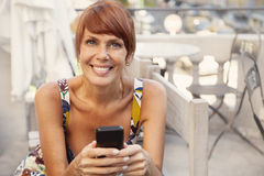 Happy adult woman smiling with mobile phone. Sending text message Royalty Free Stock Images