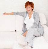 Happy adult woman on sofa Stock Photography