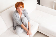 Happy adult woman on sofa Stock Photos