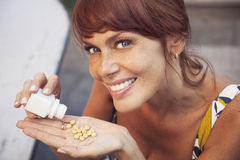 Happy adult woman taking pills. Smiling and looking at camera Royalty Free Stock Photos