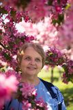 Happy adult woman under pink flowers in garden Stock Image