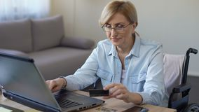 Happy adult woman in wheelchair entering card number on laptop, shopping online