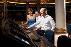 Happy adults formal dressed gambling in casino stock images
