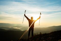 Happy adventurer, with open arms, stands on the edge of the clif. F, admiring the panorama of the mountains in the light of the setting sun. Epic travel in the Stock Images