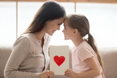 Happy mom and kid daughter holding greeting card with heart. Happy affectionate mom and cute little kid daughter holding greeting card with red heart touching stock photo