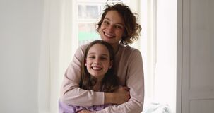 Happy affectionate young mom hugging teen daughter looking at camera
