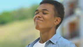Happy african-american boy breathing enjoying fresh air, outdoor walk closeup