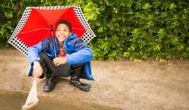 Happy African American boy with umbrella, playing with sailboat. stock photos