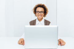 Happy african american business woman working with laptop at workplace. Portrait of happy african american young business woman sitting and working with laptop Stock Photo