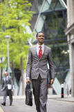 Happy African American businessman with bag walking on street Stock Images