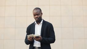 Happy african american businessman holding a big amount of money in his hands. He stands in the street near the office. Center or bank and shows money to the stock footage