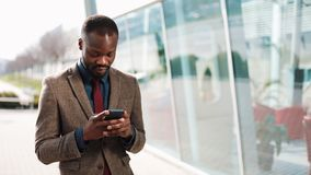 Happy African American businessman using a smartphone standing near the office building. Business, people, communication. Technology, leisure and lifestyle stock footage