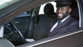 Happy African American chauffeur looking into camera, luxury transfer, service stock photo