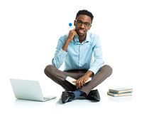 Happy african american college student sitting with laptop, book Stock Photo
