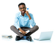 Happy african american college student sitting with laptop, book Stock Photos