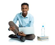Happy african american college student sitting with laptop on wh Stock Images