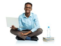 Happy african american college student sitting with laptop on wh Stock Photos