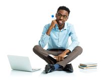 Happy african american college student sitting on white with lap Stock Photos