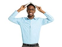 Happy african american college student standing with book on his Stock Photos
