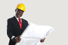 Happy african american construction worker holding blueprints Royalty Free Stock Image