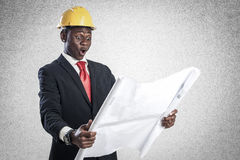 Happy african american construction worker holding blueprints Royalty Free Stock Photo