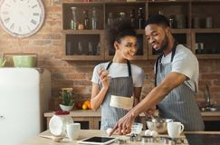 Happy african-american couple baking and using tablet Royalty Free Stock Images