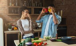 Happy african-american couple cooking and having fun in kitchen Stock Photo
