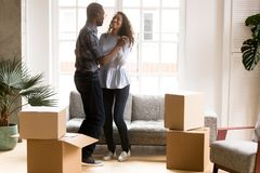 Happy African American couple dancing after moving. Happy African American couple in love dancing after moving in new house, attractive smiling women and men royalty free stock image