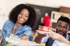 Happy african american couple eating at restaurant. Leisure, food and people concept - happy african american couple eating at restaurant Stock Photography