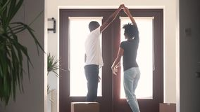 Happy african couple first time home buyers dancing in hallway