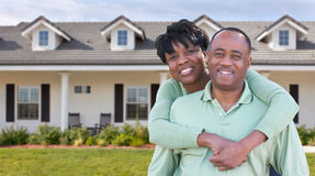 Happy African American Couple In Front of Beautiful House. royalty free stock image